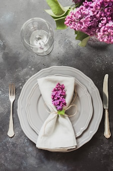 Spring elegant table place setting with violet lilac, silverware on vintage table.