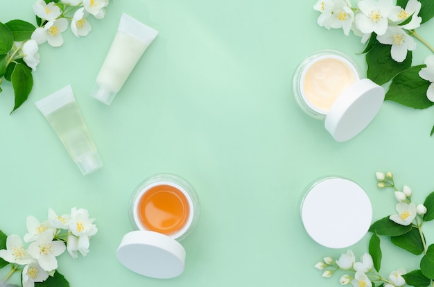 Весенний уход за лицом. баночка крем, косметический продукт с цветами жасмина. натуральная травяная органическая косметика. концепция красоты