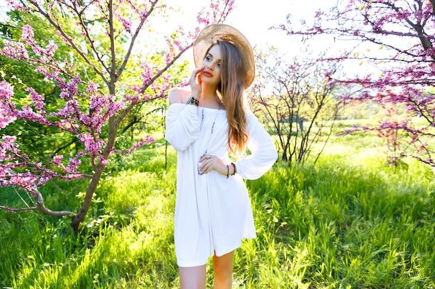 官能的な美しさの女性の春のファッションの肖像画、長い髪のパステルメイク、花の庭公園でポーズ、晴れた暑い日、白いヴィンテージのドレス、トレンディなアクセサリー。自撮り、素晴らしい笑顔、前向き