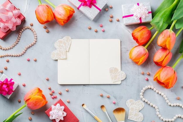 주황색 화려한 튤립, 액세서리, 선물 상자, 메이크업, 보석과 함께 봄 패션 여자 여자 배경. 세련된 여성 플랫레이 복사 공간 이미지