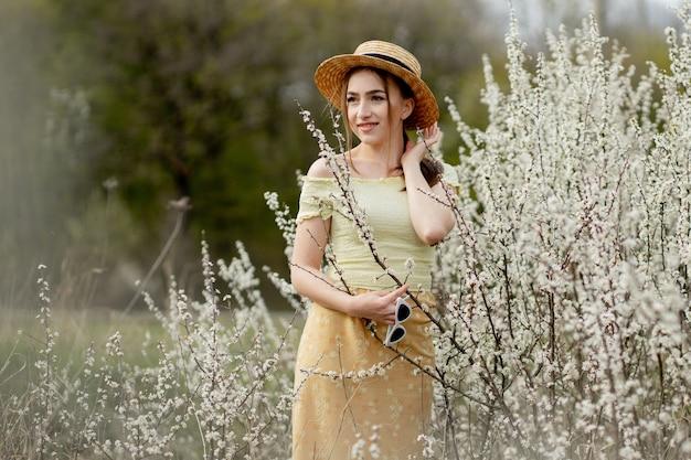春のファッションの女性が咲く屋外