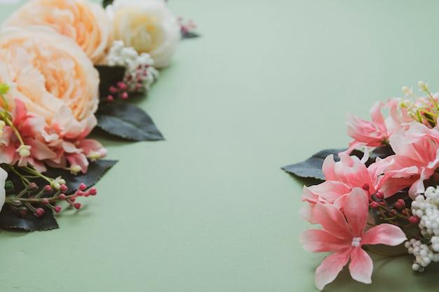 Spring feminine background, vintage flower composition on green board.