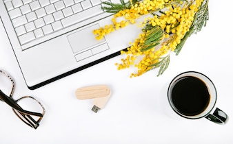Spring festive set with flowers and a laptop on a white background