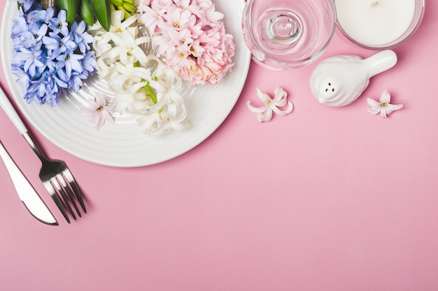 Spring festive table setting with hyacinth flowers on a pink background