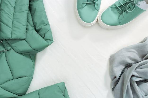 Весенняя квартира лежала от яркой теплой куртки женщин и ботинок и шарфа с космосом экземпляра на белой конкретной предпосылке. комплект женской одежды. вид сверху.