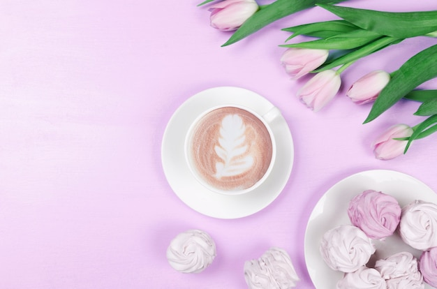Spring flat lay.white cup with coffee, pink tulips and marshmallows. top view, copy space