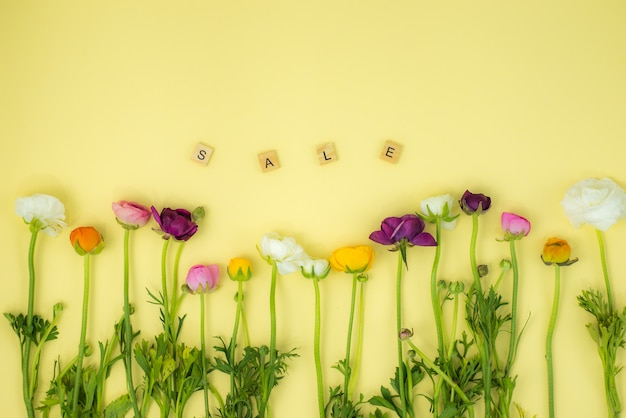Spring flatlay concept background with flowers and sale wooden word