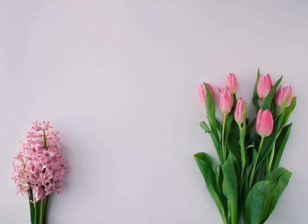 Весенняя цветочная композиция с розовыми тюльпанами и розовым гиацинтом на ярком фоне. минимальная концепция. скопируйте пространство.