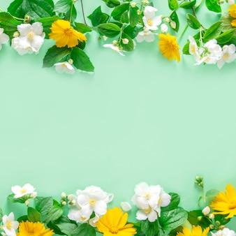 Весенний цветочный фон. цветочная рамка на фоне мяты, вид сверху.