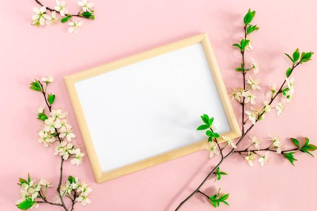 フォトフレームの周りの桜と春の花の枝。インスピレーションまたは動機付けのテキストと柔らかいピンクの背景に引用の空白の白。モックアップ、フラットレイアウトのトップビュー、コピースペース。