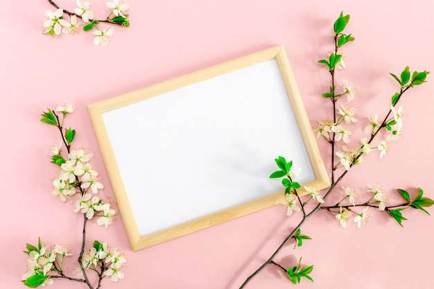 Spring floral branches with cherry blossoms around photo frame. white blank for inspirational or motivational text and quote on soft pink background. mockup, flat lay top view, copy space.