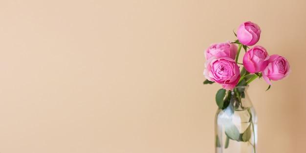 ベージュ パステル背景の花瓶に新鮮なバラの春のフラワー アレンジメント。コピースペースのあるお祝いの花のコンセプト