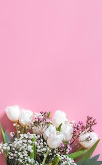 Spring flower arrangement on a pink wall