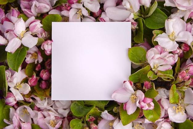 春の花のボーダー、空白の紙カード、ピンクと白の花と緑の葉のフレームとリンゴの木の枝。花の背景、トップビュー。春の花