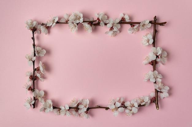 フレームのピンクの背景に春の開花枝。テンプレート。背景。モックアップ。
