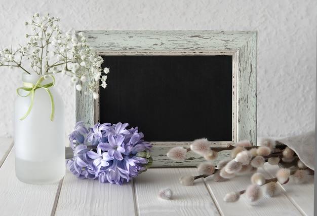 Spring flowers around a blackboard in rustic frame