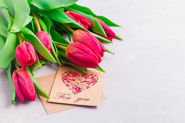 Spring flowers background. easter or mother day gift present. pink tulips on gray light table