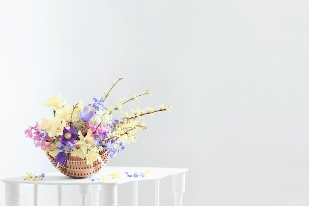 Spring flowers in basket on white interior