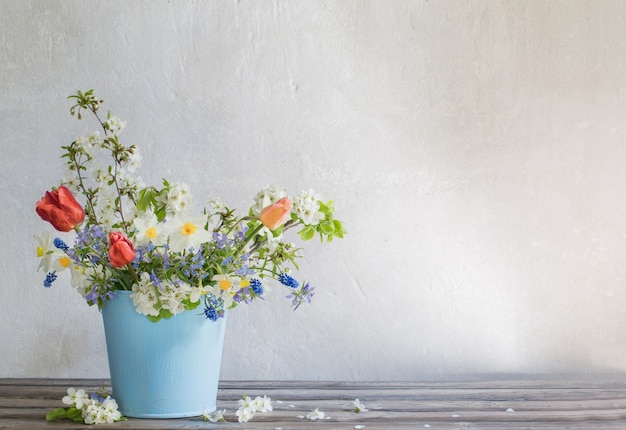 Spring flowers in blue bucket on white background