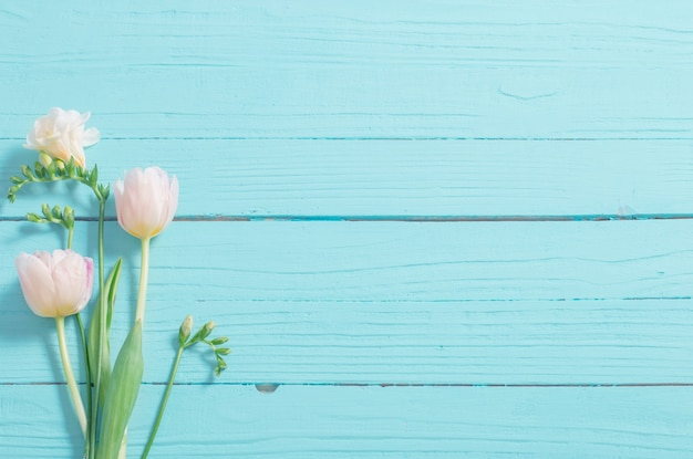 Spring flowers on blue mint wooden background