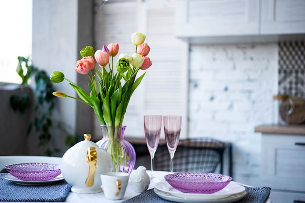 Spring flowers bouquet with beautiful purple glass crockery in the kitchen
