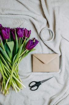 Весенние цветы, букет пурпурных тюльпанов и конверт на бежевом пледе, конверт из крафт-бумаги, ножницы и скотч.