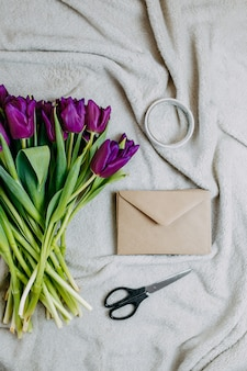 Spring flowers, bunch of purple tulips and envelope on beige plaid, envelope of craft paper, scissors and tape flat lay.