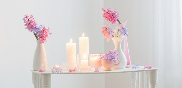 Spring flowers and burning candles in white interior