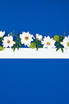 春の花の組成。コピースペース付きの紙カードのモックアップ。青い空間に白い花で作られたフレーム。