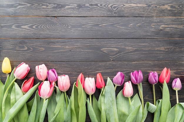 봄, 꽃 개념. 검은 나무 테이블 배경 위에 colorfull 튤립