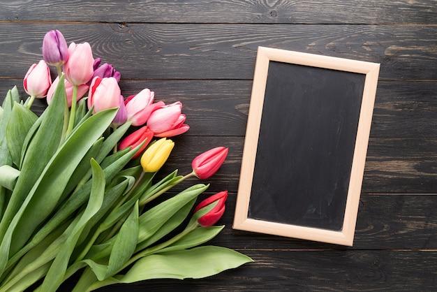 봄, 꽃 개념. 검은 나무 테이블 배경 위에 빈 칠판과 colorfull 튤립