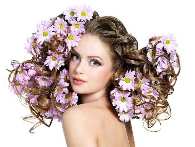 若い美しい女性のゴージャスな長い巻き毛の春の花-白いスペース