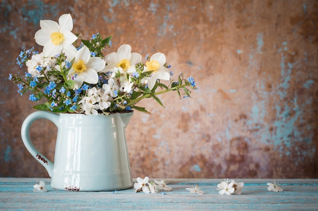 Весенние цветы в кувшине на старый деревянный расписной стол