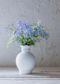 표면 흰색 오래 된 벽에 꽃병에 봄 꽃