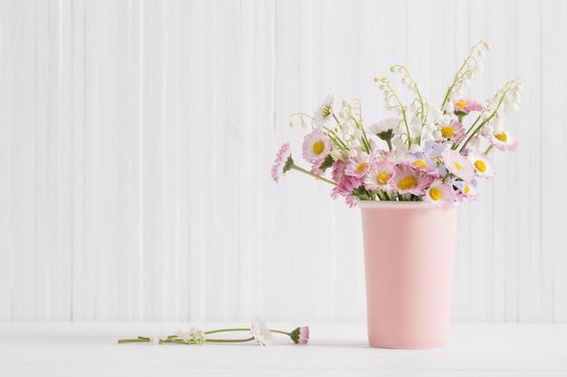 Весенние цветы в вазе на белом фоне деревянные
