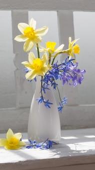 白い木製のベンチの上に花瓶の春の花