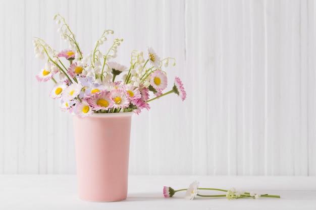 흰 나무 벽에 꽃병에 봄 꽃