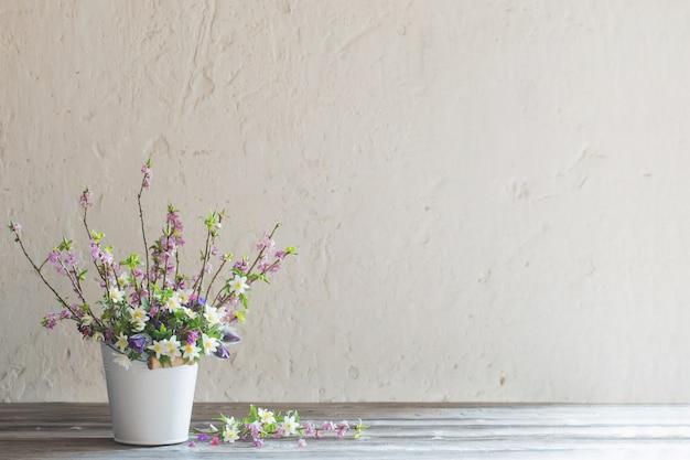배경 오래 된 흰 벽에 흰색 양동이에 봄 꽃