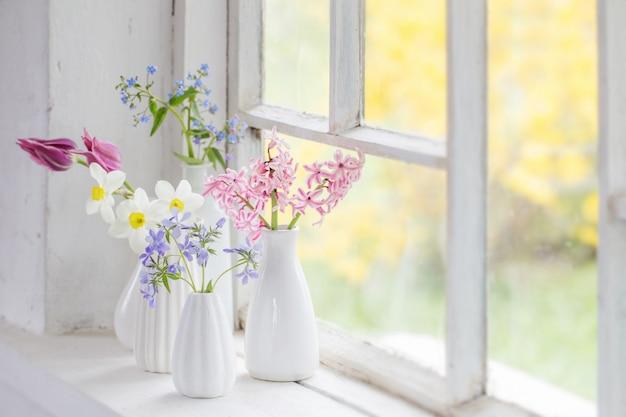 오래 된 창턱에 흰색 꽃병에 봄 꽃
