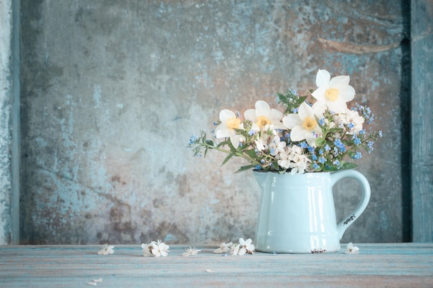 Spring flowers in jug on old wooden painted background