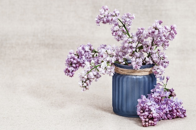 Spring flowers of lilac in vase on rustic tablecloth with copy space.