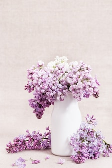 Spring flowers of lilac white and purple colored in vase on rustic tablecloth with copy space. lilac closeup.