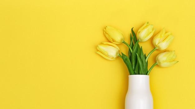 노란색 배경에 흰색 세라믹 꽃병에 튤립의 봄 꽃. 자연 꽃 배경