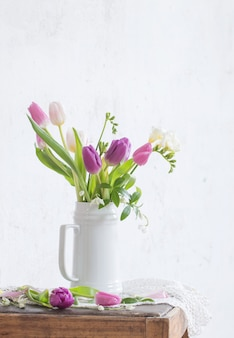 Spring flowers on old chair on background old white wall