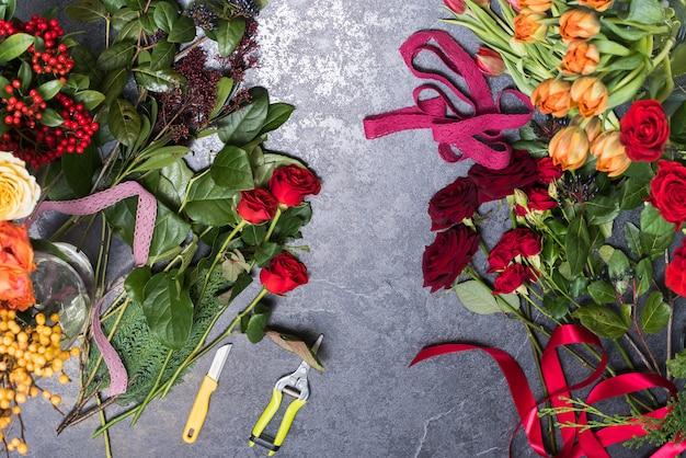 石のテーブルの春の花。バラの花束、チューリップを作成するコンセプト。職場の花屋