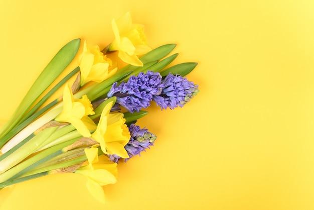 Весенние цветы на желтом столе.