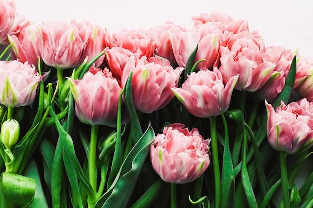 ホリデーギフトのグリーティングカードと花のフラットレイの概念として大理石の背景に春の花