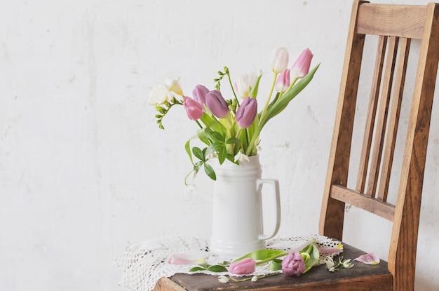 背景の古い白い壁の古い椅子に春の花