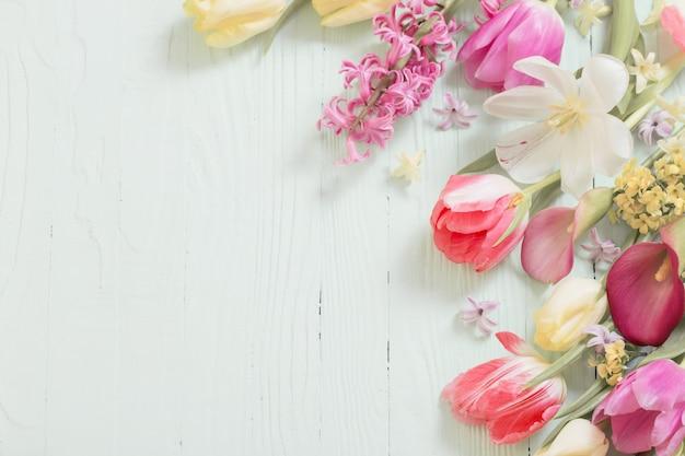 白い木製の背景に春の花