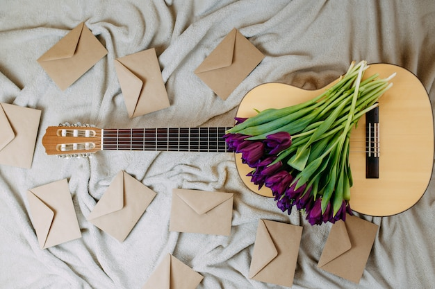 Spring flowers, purple tulips, white guitar and flowers on gray background, spring music poster, bunch of purple tulips on the guitar, envelopes of craft paper.
